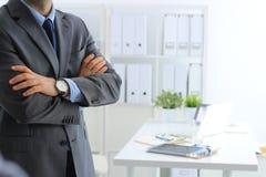 Бизнесмен стоя при оружия пересеченные в офис Стоковая Фотография