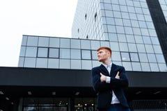 Бизнесмен стоя при оружия сложенные outdoors Стоковое Изображение