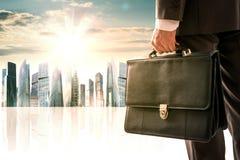 Бизнесмен стоя с задней частью против города стоковое фото