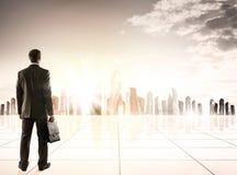 Бизнесмен стоя с задней частью против города стоковое изображение rf