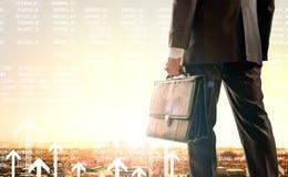 Бизнесмен стоя с задней частью против города стоковая фотография rf