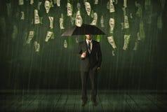 Бизнесмен стоя с зонтиком в концепции дождя долларовой банкноты Стоковое фото RF