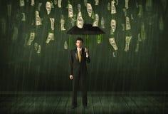 Бизнесмен стоя с зонтиком в концепции дождя долларовой банкноты Стоковое Изображение