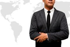 Бизнесмен стоя с картой мира в предпосылке стоковое фото