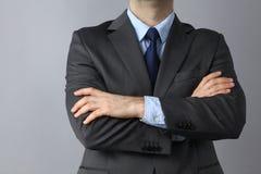 Бизнесмен стоя с оружиями пересек изолированный на серой предпосылке Стоковое Изображение