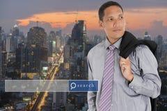 Бизнесмен стоя с предпосылкой города нерезкости с engi поиска стоковая фотография