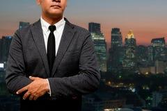 Бизнесмен стоя с светом города в предпосылке стоковая фотография