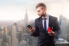 Бизнесмен стоя с чашкой кофе и телефоном стоковые фотографии rf