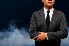 Бизнесмен стоя с дымом в предпосылке стоковая фотография