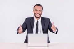 бизнесмен счастливый Усмехаясь африканский бизнесмен сидя на столе Стоковая Фотография RF