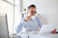 Бизнесмен с бумагами выпивая кофе на офисе Стоковое Изображение