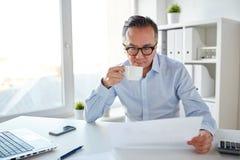 Бизнесмен с бумагами выпивая кофе на офисе Стоковые Изображения
