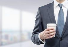Бизнесмен с бумажной кофейной чашкой в офисе Стоковое Изображение
