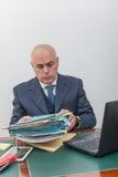 Бизнесмен с вашими файлами и обработкой документов на столе, в офисе Стоковые Изображения RF