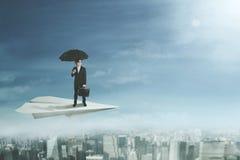 Бизнесмен с зонтиком на самолете бумаги иллюстрация штока