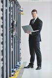 Бизнесмен с компьтер-книжкой в комнате сервера сети Стоковое Изображение