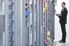 Бизнесмен с компьтер-книжкой в комнате сервера сети Стоковое фото RF