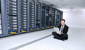 Бизнесмен с компьтер-книжкой в комнате сервера сети Стоковые Фотографии RF