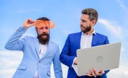 Бизнесмен с компьтер-книжкой серьезной пока стекла делового партнера смешные смотрят смешными Как предпринимательство игры стопа стоковое изображение