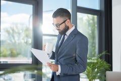 Бизнесмен с кофейной чашкой в руке анализируя бумаги в офисе Стоковые Фотографии RF