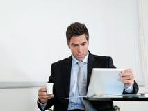 Бизнесмен с кофейной чашкой используя таблетку цифров Стоковое Изображение