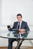 Бизнесмен с кофейной чашкой используя таблетку цифров Стоковые Фотографии RF