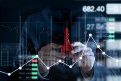 Бизнесмен с красным ключом для успеха в руках на красочной предпосылке фондовой биржи диаграмм и диаграмм Стоковое Изображение RF