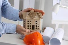 Бизнесмен с миниатюрой дома в руке Стоковое Фото