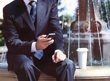 Бизнесмен с мобильным телефоном и кофе около фонтана Стоковая Фотография