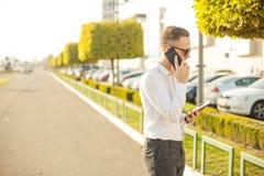 Бизнесмен с мобильным телефоном и таблеткой в руках Стоковые Изображения