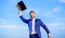 Бизнесмен с ожиданием компьтер-книжки пока соединитесь с интернетом Искать сеть wifi Бизнесмена костюма небо outdoors стоковые фото