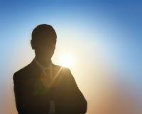 Бизнесмен с оружиями пересек на предпосылку неба захода солнца, силуэты Стоковое Изображение