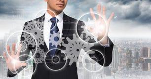 Бизнесмен с пирофакелами на графиках шестерни рук касающих белых против горизонта Стоковая Фотография