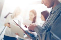 Бизнесмен с планшетом в офисе Женщины коллективно обсуждать на предпосылке стоковое фото rf