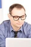 Бизнесмен с портативным компьютером в офисе Стоковая Фотография RF