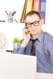 Бизнесмен с портативным компьютером в офисе Стоковая Фотография