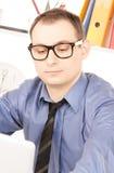 Бизнесмен с портативным компьютером в офисе Стоковые Изображения
