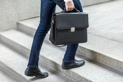 Бизнесмен с портфелем в руке идя вверх на лестницы Стоковые Фотографии RF