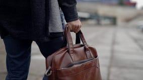 Бизнесмен с портфелем, идя через город Человек идет вниз по улице на дело акции видеоматериалы