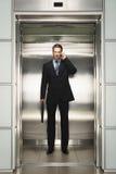 Бизнесмен с портфелем используя мобильный телефон в лифте Стоковое фото RF
