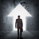 Бизнесмен с портфелем шагая через дверь Стоковая Фотография
