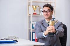 Бизнесмен с призовой чашкой для достижений в офисе стоковые изображения