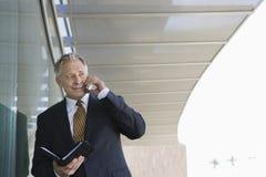 Бизнесмен с плановиком дня пока на звонке Стоковое Фото