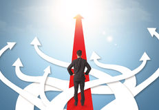 Бизнесмен с различными стрелками направления Стоковая Фотография