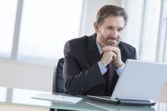 Бизнесмен с руками на Chin смотря компьтер-книжку в офисе Стоковое Изображение