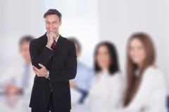 Бизнесмен с рукой на подбородке стоя в зале заседаний правления Стоковое Изображение