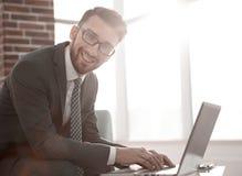 Бизнесмен с стеклами сидит на столе в офисе стоковая фотография rf