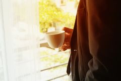 Бизнесмен с стойкой и держать костюма кофейную чашку стоковое фото rf