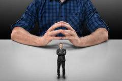 Бизнесмен с сложенными оружиями стоит перед большим усаживанием человека Стоковая Фотография RF