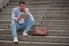 Бизнесмен с таблеткой на предпосылке лестниц Работник говоря на телефоне Концепция деловой беседы скопируйте космос Стоковое Изображение